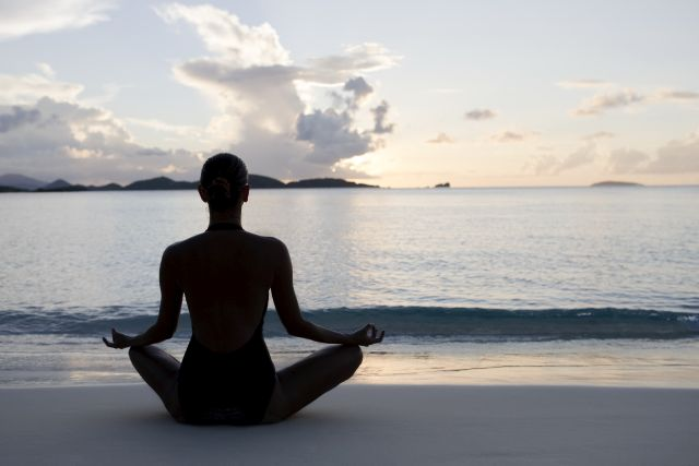 woman practicing yoga at a beach during sunset