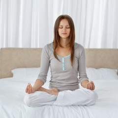 Young woman doing yoga exercises on the bed at home